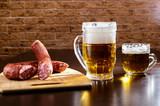 Two mugs of beer and smoked sausage on the table. - 206068464
