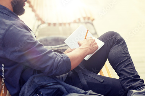 Wall mural lifestyle, freelance, inspiration and people concept - close up of man with bag writing to notebook or diary sitting on city street bench