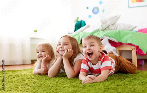 Foto Murales childhood, leisure and family concept - happy little kids lying on floor or carpet