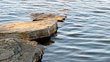 Stepping stones of flat natural rock leading out into beautiful lake