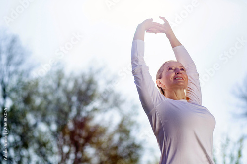 Foto Murales Morning gymnastics. Nice cheerful woman holding her hands up while doing morning exercises
