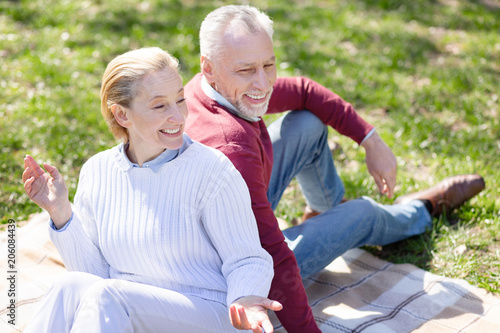 Pleasurable weekend. Cheerful delighted couple having a picnic while resting in the park together