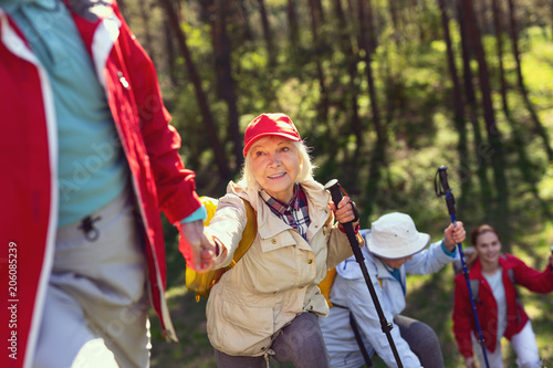 Feeling great. Delighted blond woman giving a hand and hiking with her friends
