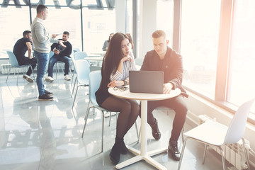 Beautiful young business couple are using a laptop, talking and smiling while working in office