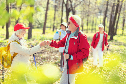 Fotobehang Geel My gift. Cheerful aged man smiling and giving a flower to a woman while hiking