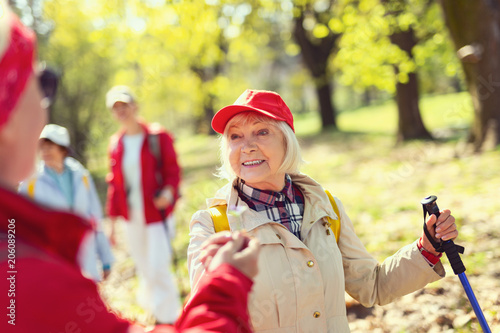 Plexiglas Geel I feel great. Inspired aged woman smiling and looking at the man while hiking