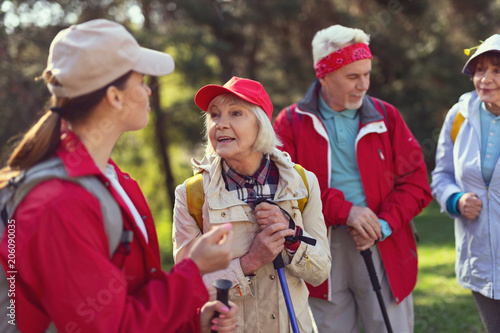 Canvas Zalm Having a walk. Cheerful blond woman smiling and talking with the guide while hiking