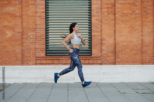 Fototapeta Young woman running in the city