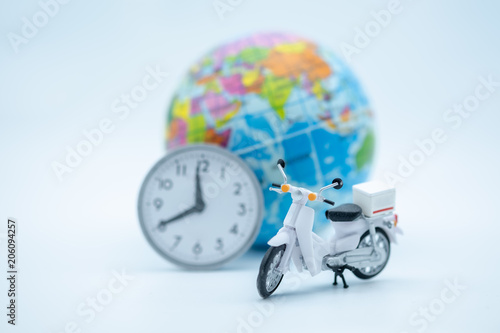 Aluminium Scooter Travel and transport concept. Close up of miniature motercycle scooter model figure with vintage round clock and mini world ball on white background.