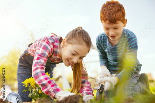 Poster Pleasurable time. Delighted positive children having fun while working in the garden together