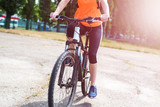 Young woman riding a bicycle in a bright orange shirt, close-up. - 206101888