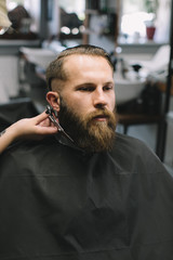 Getting perfect shape. Close-up side view of young bearded man getting beard haircut by hairdresser at barbershop