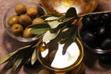 Bottle virgin olive oil and oil in a bowl with some olives - 206116613