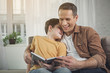 Leinwanddruck Bild - Joyful parent is embracing boy while holding a book. They are sitting on couch and smiling