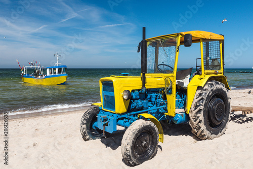 Fotobehang Trekker Old tractor on the beach and fishing boat on the sea