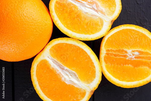 Fruits of oranges on a black wooden background, halves of oranges on wooden boards. Citrus for Vegetarian Breakfast