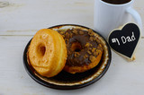 Donuts, or doughnuts, on a brown ceramic plate with a cup of coffee on a whitewahed rustic table top. Good image for donuts and dads for father's day in June. - 206138097