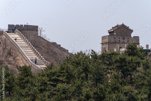 Plexiglas Peking Beijing, China - April 28, 2010: Great Wall of China at Badaling. Stretch of the wall with people climbing stairs and tower structure. Green forest in front, all under light blue sky.