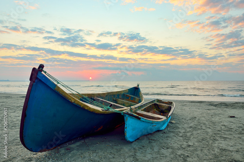 Foto Murales Fishing boats on the beach at sunrise