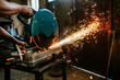 Cutting metal with angle grinder in workshop.