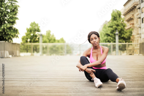 Sticker Sporty woman sitting on the ground