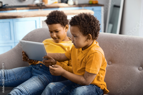 Lazy pastime. Pleasant little boys sitting on the sofa and watching a cartoon on the tablet together, enjoying their free time