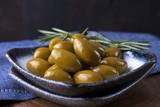 Оливки целые с веточкой розмарина на блюде .