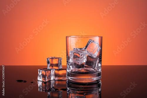 Pusty szkło z lodem przygotowywającym dla napoju na ciepłym zmroku - pomarańczowy tło