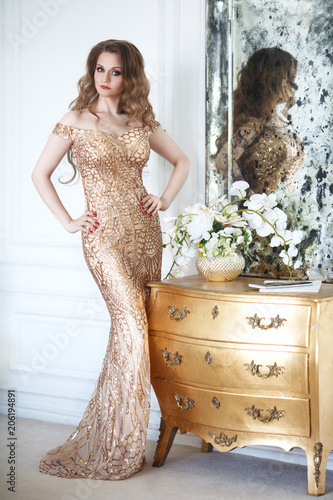 Slender elegant woman in an evening long gold dress in a chic interior.