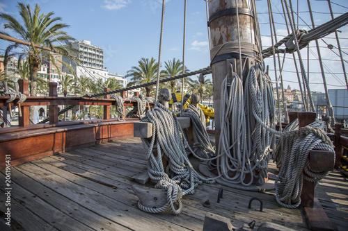 Fotobehang Schip Mast, ropes and rigging on the galleon Neptune built for a Roman Polansky film with a view over the deck of Genoa, Italy