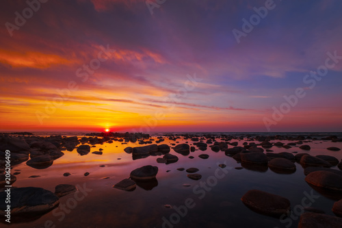 Foto Murales Beautiful sunset at sea side with stones at foreground