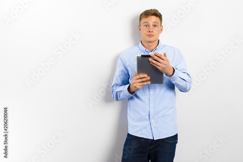 Young man looking up and standing against white wall.