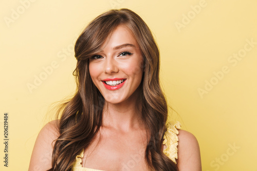Photo closeup of adorable young woman 20s having long brown hair and red lips smiling to you with perfect white teeth, isolated over yellow background