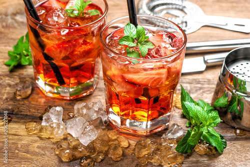 Fototapeta Red drink strawberry mint leaves ice Cocktail making bar accessories
