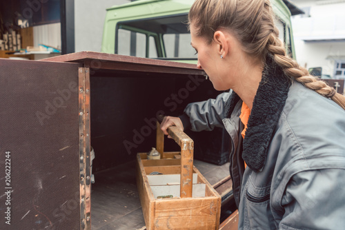 Woman carpenter loading tools in mobile workshop transporter in the morning