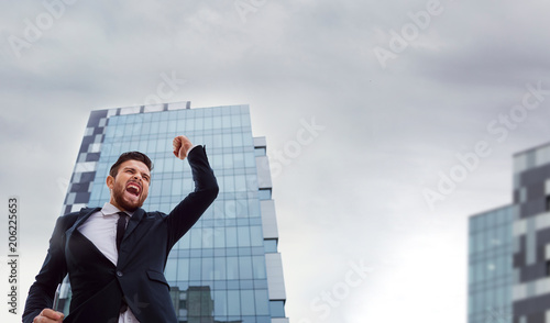Foto Murales Happy businessman on a business building background.
