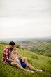 Quadro Loving couple sitting  hugged on grass in the mountain
