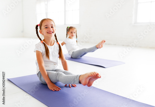children girls doing yoga and gymnastics in gym