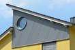 Leinwanddruck Bild - Seitliche Verkleidung des oberen Stockwerks mit verzinktem und RundfensterWellblech er Stehfalz-Metall-Dachabschluss, Zinkblech-Dachrinne und Schneefang an einem Wohnhausdach