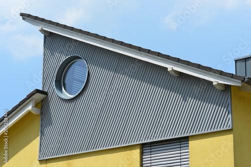 Leinwanddruck Bild Seitliche Verkleidung des oberen Stockwerks mit verzinktem und RundfensterWellblech er Stehfalz-Metall-Dachabschluss, Zinkblech-Dachrinne und Schneefang an einem Wohnhausdach
