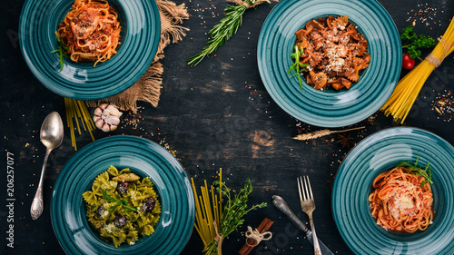 A set of cooked pastes in plates. On a wooden background. Italian cuisine. Top view. Copy space.
