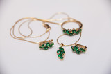 set of gold earrings, ring and pendant with emeralds
