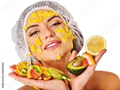 Facial mask from fresh fruits for woman. Girl in medical hat bit slices of kiwi and hold plate with fruit salad. Green plants on backgrounds in spa salon. Selfie in spa salon.
