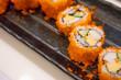 Quadro California maki sushi roll on black plate, japanese food