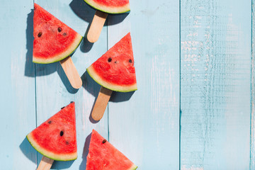 Slices of watermelon on blue wooden desk.