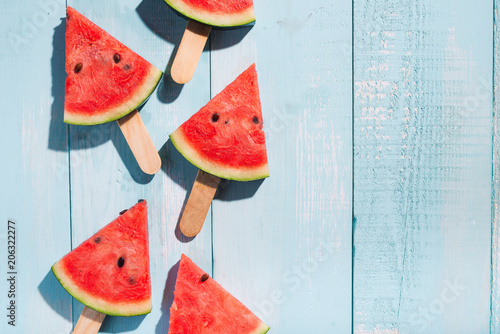 Wall mural Slices of watermelon on blue wooden desk.