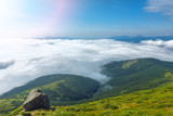 Landscape of Carpathian Mountains in a summer sunny day. Beautiful mountain scenery with clear sky and a rock.