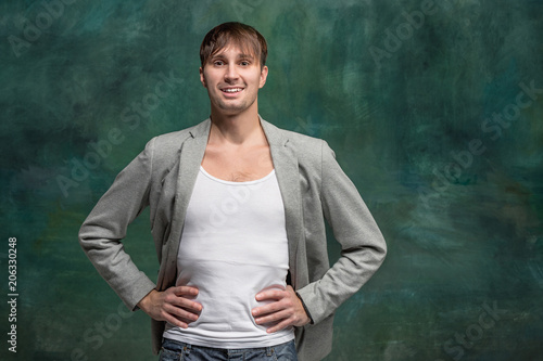The happy man standing and smiling against studio background.