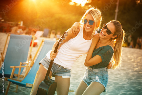 Two young female friends hangout at the beach ,singing and relaxing in beautiful summer sunset.They hug each other.Best friends.