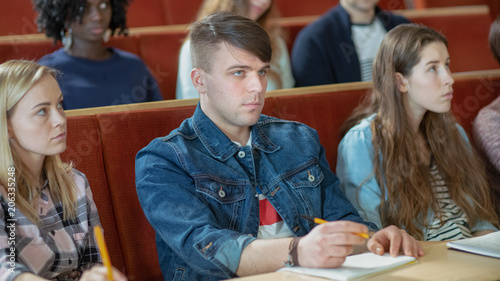 Beautiful and Intelligent Young Caucasian Man Listens to a Lecture in a Classroom Full of Multi Ethnic Students.